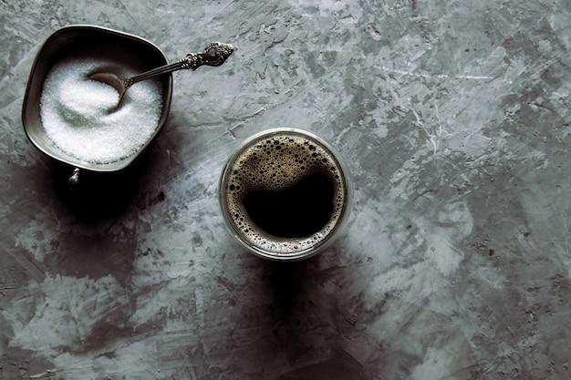 Szklany kubek świeżej kawy z łyżką brązowego cukru