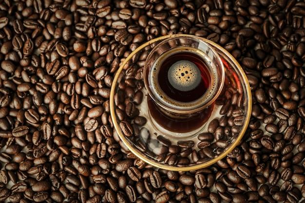 Szklany kubek w tradycyjnym tureckim stylu z czarną kawą stoi na leżących na stole ziarnach kawy. pyszny napój energetyczny.