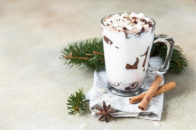 Szklany kubek z gorącą czekoladą lub napojem kakaowym i laski cynamonu z anyżem
