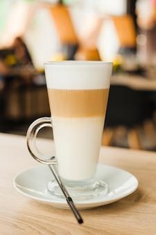 Szklany kubek z gorącym latte na drewnianym stole w kafeterii
