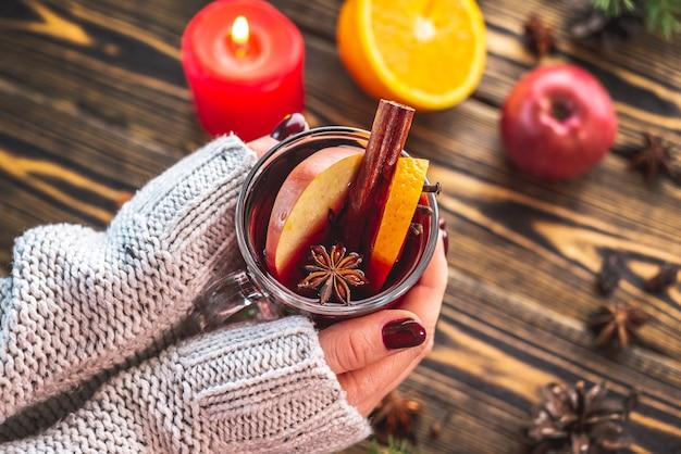 Szklany kubek z grzanym winem ozdobiony cynamonem, anyżem i owocami