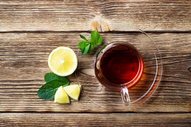 Szklany kubek z herbatą, miętą i cytryną na drewnianym stole w stylu rustykalnym, widok z góry