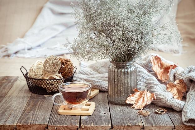 Szklany kubek z herbatą na drewnianym stole z detalami jesiennego wystroju i suszonymi kwiatami w wazonie.