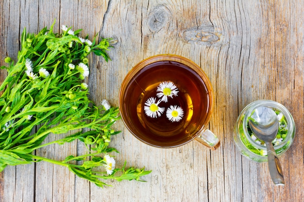 Szklany kubek z herbatą z apteki rumiankowej, bukiet apteki z kwiatów rumianku i szklany słoik