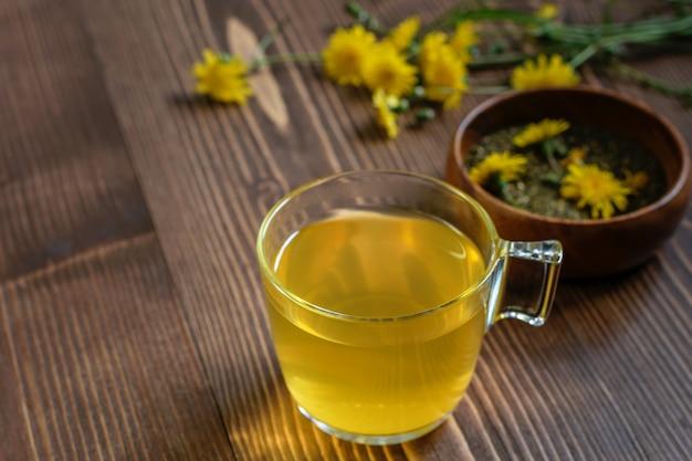 Szklany kubek z herbatą z kwiatów mniszka lekarskiego. suche liście herbaty i świeże kwiaty mniszka lekarskiego na drewnianym stole, przygotowane do ceremonii parzenia herbaty.