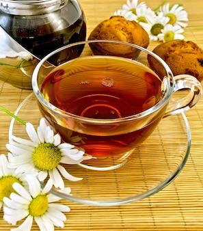 Szklany kubek z herbatą ziołową, czajnik, dwie babeczki, rumianek na bambusowej serwetce
