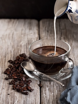 Szklany kubek z kawą, mleko przelewa się z rocznika mleczarza. kawowe fasole na drewnianym stole. zbliżenie.