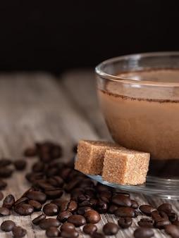 Szklany kubek z kawą z mlekiem, kawą latte. cukier trzcinowy na spodku. kawowe fasole na drewnianym stole. zbliżenie.
