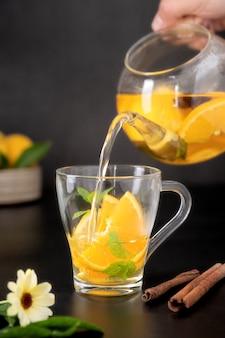 Szklany kubek z owocową herbatą ziołową na czarnym tle. zdrowa gorąca herbata z nagietka