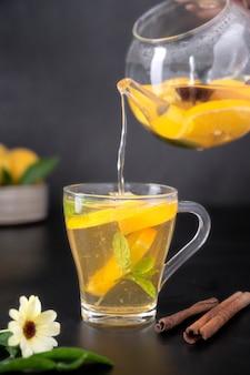 Szklany kubek z owocową herbatą ziołową na czarnym tle. zdrowa herbata z nagietka