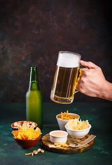 Szklany kubek z piwem z pianką i kroplami wody oraz przekąskami na ciemnozielonym