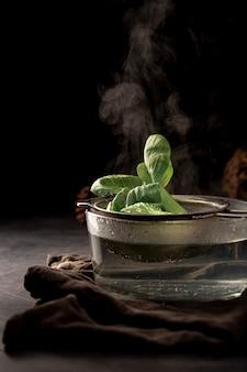 Szklany kubek z siatką i liśćmi herbaty