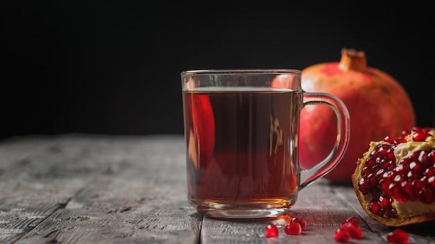 Szklany kubek z sokiem z granatów i świeżymi granatami na drewnianym stole. napój przydatny dla zdrowia.