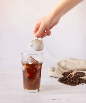 Szklany kubek z zimną kawą i lodem, kawa ziarnista