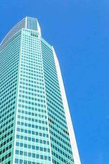 Szklany nowoczesny wieżowiec budynku naprzeciwko błękitnego nieba w widoku perspektywicznym