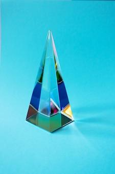Szklany pryzmat piramidy na niebieskim tle z kolorowym odbiciem światła, pionowy