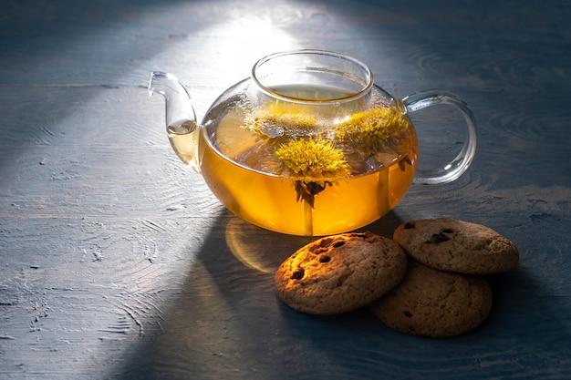 Szklany przezroczysty czajniczek ze zdrową herbatą ziołową z żółtego mniszka lekarskiego i ciasteczka owsiane z rodzynkami na niebieskim drewnianym tle, oświetlony słońcem, niski klucz. koncepcja dnia herbaty