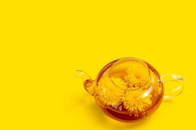 Szklany przezroczysty czajniczek ze zdrową herbatą ziołową z żółtego mniszka lekarskiego na żółtym tle. ziołowy napój przyjazny dla środowiska, zdrowy styl życia. koncepcja międzynarodowego dnia herbaty