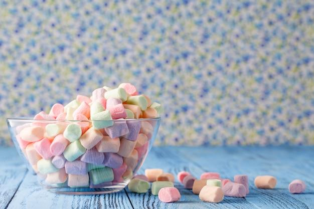 Szklany puchar barwioni marshmallows na błękitnym tle ,.
