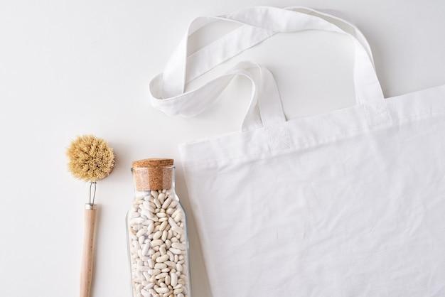 Szklany słoik, drewniana szczotka i torba na zakupy. koncepcja zero odpadów.