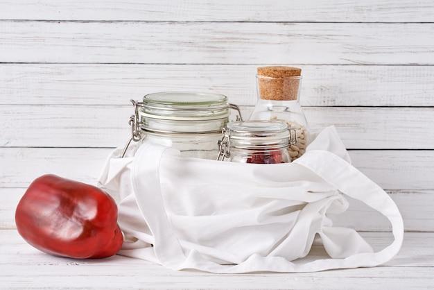 Szklany słoik, drewniana szczotka i torba na zakupy