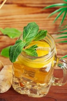 Szklany słoik ice zielonej herbaty z limonką, cytryną, miętą na drewnianym stole.