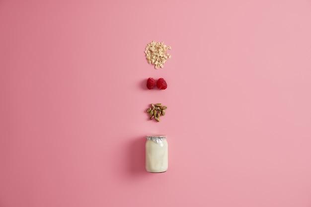 Szklany słoik jogurtu, pistacji, czerwonej maliny i płatków zbożowych do zmieszania i zjedzenia. różowe tło. zdrowe śniadanie dietetyczne. naturalne składniki na owsiankę lub szybką przekąskę. posiłek wegetariański