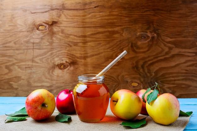 Szklany słoik miodu z łyżką i świeżymi jabłkami, miejsce. koncepcja rosz haszana. żydowskie symbole nowego roku.