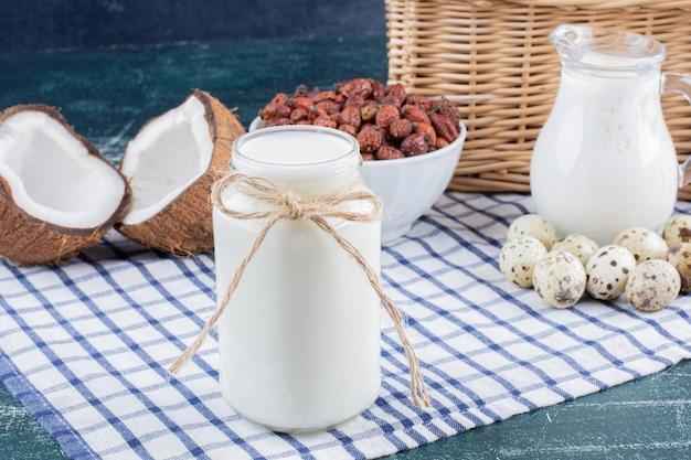 Szklany słoik mleka, suszonych daktyli i jaj przepiórczych na marmurowym stole.