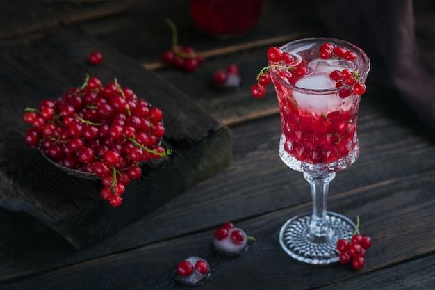 Szklany słoik napoju sodowego z czerwonej porzeczki na ciemnym drewnianym stole. letnia zdrowa lemoniada detoksykacyjna, koktajl lub inny napój. niska zawartość alkoholu, napoje bezalkoholowe, koncepcja diety wegetariańskiej lub zdrowej.