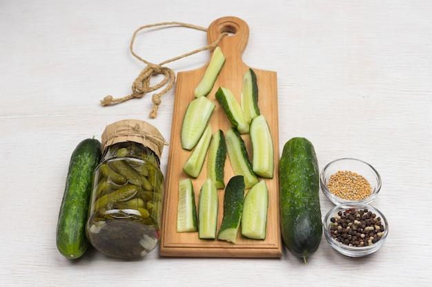 Szklany słoik ogórków konserwowych, ogórków świeżych, zielonej pietruszki, czosnku i przypraw. domowe produkty fermentacji. zdrowa żywność zimowa. biała powierzchnia. widok z góry. skopiuj miejsce