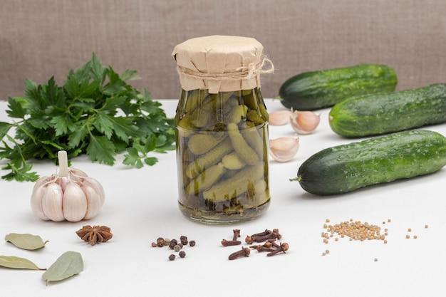 Szklany słoik ogórków konserwowych, ogórków świeżych, zielonej pietruszki, czosnku i przypraw. domowe produkty fermentacji. zdrowa żywność zimowa. biała powierzchnia.
