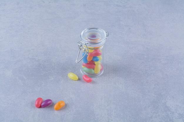 Szklany słoik pełen kolorowych cukierków fasolowych