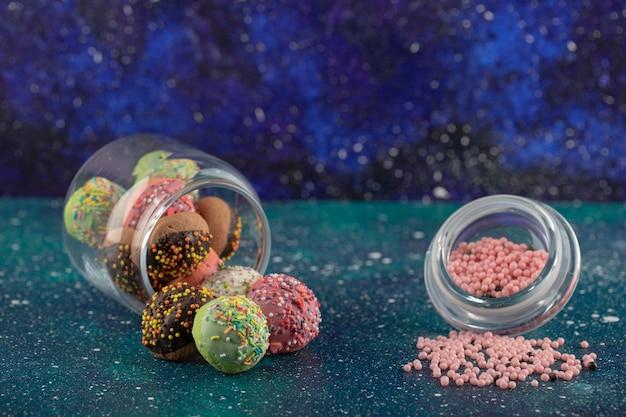 Szklany słoik pełen małych kolorowych pączków.