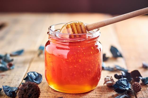 Szklany słoik pełen miodu. biorąc miód drewnianą łyżką