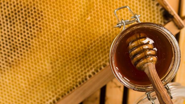 Szklany słoik pełen miodu z łyżką miodową