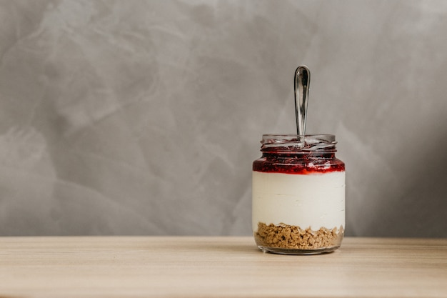 Szklany słoik pełen płatków śniadaniowych, jogurtu i dżemu owocowego z łyżeczką w środku