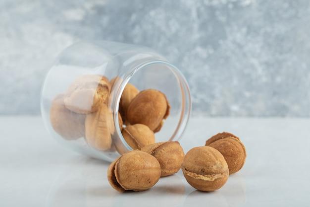 Szklany słoik pełen słodkich ciasteczek w kształcie orzecha włoskiego.