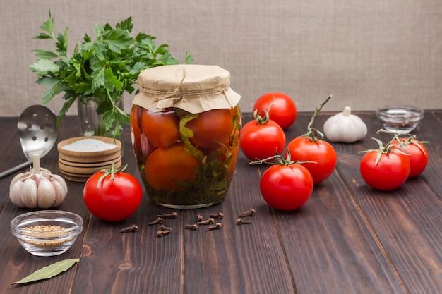Szklany słoik pomidorów z puszki, świeżych pomidorów, zielonej pietruszki, czosnku i przypraw. domowe produkty fermentacji. zdrowa żywność zimowa. . skopiuj miejsce