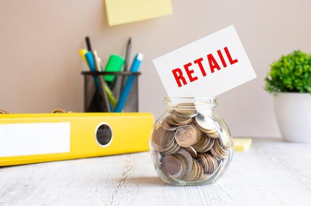 Szklany słoik wypełniony jest monetami. powyżej na brzegu kartka z napisem retail. budżet inwestycyjny.