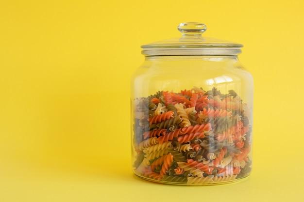 Szklany słoik wypełniony kolorowym makaronem spiralnym na żółtym tle