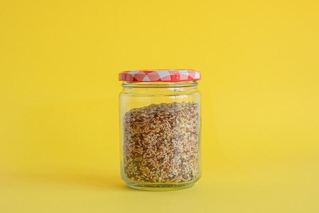 Szklany słoik wypełniony płatkami zbożowymi na żółtym tle
