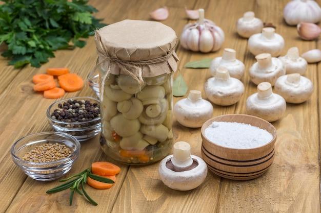 Szklany słoik z grzybami konserwowymi i świeżymi pieczarkami. przyprawa: sól, czosnek, cebula, liść laurowy na stole. zdrowe odżywianie zimowe. domowe produkty fermentacji. jasna drewniana powierzchnia