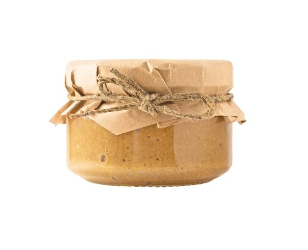 Szklany słoik z hummusem z masłem orzechowym lub tahini z pastą sezamową z nakrętką pokrytą papierem