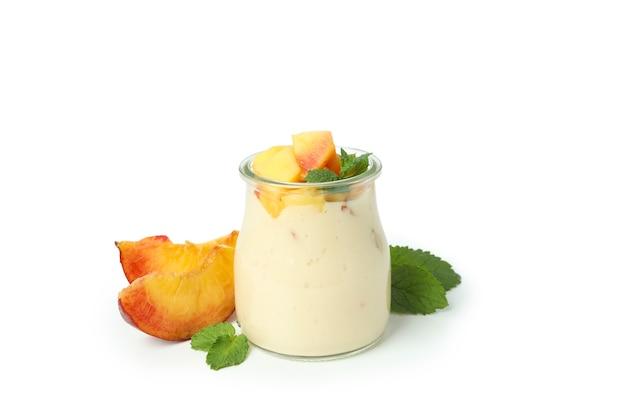 Szklany słoik z jogurtem brzoskwiniowym na białym tle