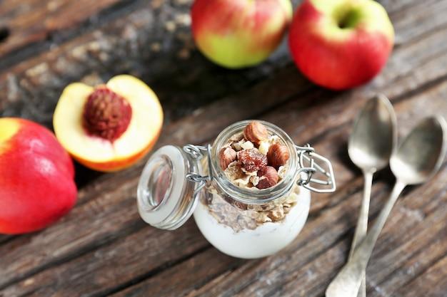 Szklany słoik z jogurtem, granollą i orzechami migdałowymi. nektarynka i jabłka są na drewnianym podkładzie z łyżkami zamkniętymi w słoiku.