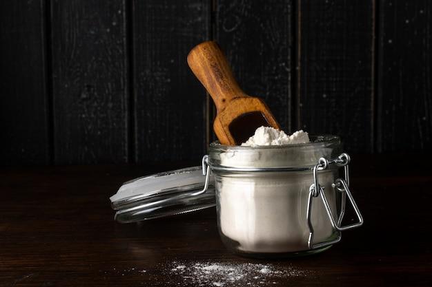 Szklany słoik z mąką i drewnianą łyżką na starym rustykalnym stole.