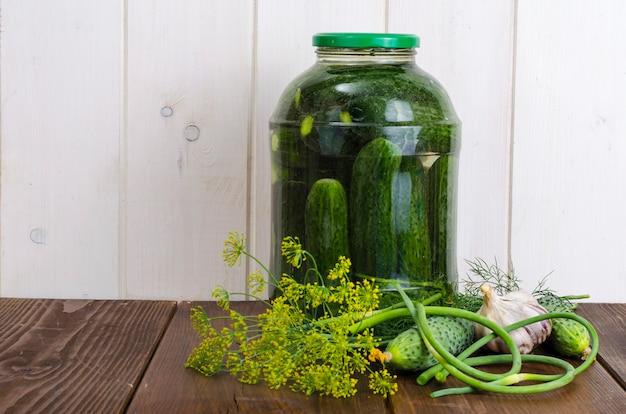 Szklany słoik z marynowanymi ogórkami i ziołami