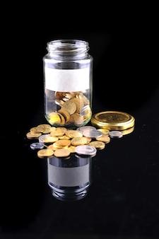 Szklany słoik z monetami na czarnym tle