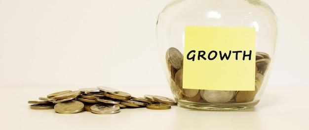 Szklany słoik z monetami na oszczędności. napis growth na papierze firmowym.